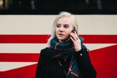 Mujer rubia sonriente de los jóvenes que habla en el teléfono en el fondo de la tranvía Retrato al aire libre de una muchacha Fotografía de archivo