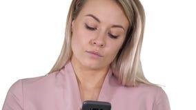 Mujer rubia sonriente de moda que usa su teléfono móvil que sonríe como ella mecanografía un mensaje de texto en el fondo blanco metrajes