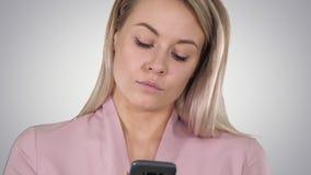 Mujer rubia sonriente de moda que usa su tel?fono m?vil que sonr?e como ella mecanograf?a un mensaje de texto en fondo de la pend metrajes