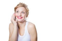 Mujer rubia sonriente feliz joven que invita al móvil Imagen de archivo libre de regalías