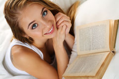 Mujer rubia sonriente hermosa joven que miente en libro de lectura de la cama Foto de archivo libre de regalías