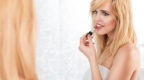 Mujer rubia sonriente que aplica el lápiz labial en espejo Imágenes de archivo libres de regalías