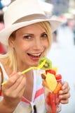 Mujer rubia sonriente que come las frutas frescas en calle Fotos de archivo