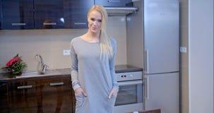 Mujer rubia sonriente que presenta en la cocina metrajes