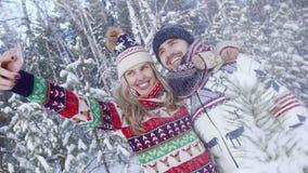 Mujer rubia sonriente y hombre joven hermoso que toman la foto de ellos mismos en bosque nevoso metrajes
