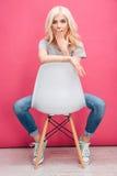 Mujer rubia sorprendente que se sienta en la silla Foto de archivo libre de regalías