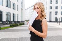 Mujer rubia sorprendida que lleva a cabo documentos Expresiones faciales vivas fotografía de archivo libre de regalías