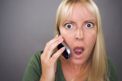 Mujer rubia Stunned que usa el teléfono celular Imagen de archivo