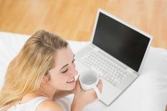 Mujer rubia tranquila que sostiene una taza que miente en cama al lado de su ordenador portátil Fotografía de archivo libre de regalías
