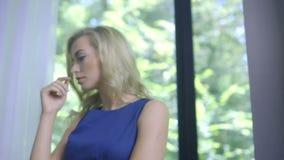 Mujer rubia triste que se coloca en la ventana que espera alguien almacen de metraje de vídeo
