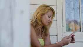 Mujer rubia triste que usa el teléfono en el pórtico de la casa blanca almacen de metraje de vídeo