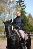 Mujer rubia y caballo negro Fotos de archivo