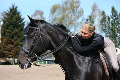 Mujer rubia y caballo negro Imagen de archivo libre de regalías