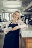 Mujer rubio-cabelluda agradable madura que se coloca en su propio restaurante fotos de archivo libres de regalías