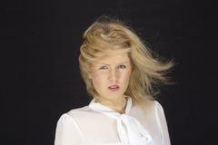 mujer Rubio-cabelluda con la blusa blanca en una tormenta (máquina de viento) Foto de archivo libre de regalías