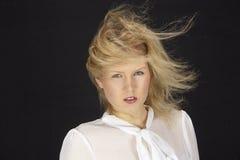 mujer Rubio-cabelluda con la blusa blanca en una tormenta (máquina de viento) Imagen de archivo