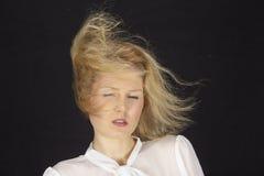 mujer Rubio-cabelluda con la blusa blanca en una tormenta (máquina de viento) Imagen de archivo libre de regalías