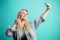Mujer rubio-cabelluda positiva que toma el selfie en el fondo azul aislado que se ríe consigo misma Imagen de archivo