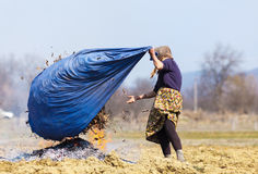 Mujer rural mayor que quema las hojas caidas Fotografía de archivo libre de regalías
