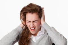 mujer 20s que consigue enojada en el problema del zumbido o la música ruidosa imagenes de archivo