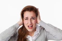 mujer 20s subrayada por el ruido, cubriendo sus oídos fotos de archivo