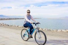 Mujer sana biking a lo largo de la costa fotografía de archivo
