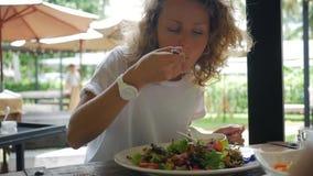 Mujer sana de la forma de vida que come la ensalada verde fresca en restaurante vegetariano HD a cámara lenta Phangan, Tailandia metrajes