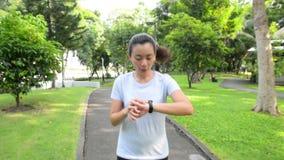 Mujer sana de la forma de vida en la ropa de deportes que funciona con y que mira su reloj en el parque en la puesta del sol