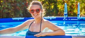 Mujer sana feliz en piscina en gafas de sol Foto de archivo