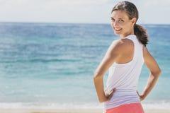 Mujer sana feliz que hace calentamiento en la playa imagen de archivo