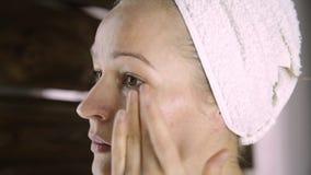 Mujer sana hermosa en una toalla que pone la crema hidratante en cara Cuidado de piel y balneario casero almacen de video