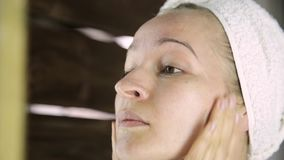 Mujer sana hermosa en una toalla que pone la crema hidratante en cara Cuidado de piel y balneario casero almacen de metraje de vídeo
