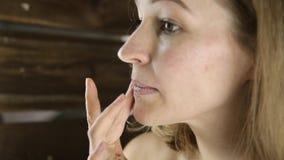 Mujer sana hermosa en una toalla que pone la crema hidratante en los labios Cuidado de piel y balneario casero almacen de video