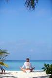 Mujer sana hermosa joven que hace la meditación en la playa Fotos de archivo libres de regalías