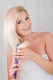 Mujer sana joven que aplica el pelo con brocha largo foto de archivo libre de regalías