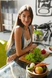 Mujer sana que come verduras en cocina Dieta de la pérdida de peso imagen de archivo libre de regalías