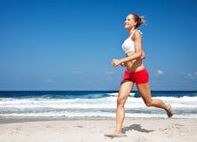 Mujer sana que corre en la playa Imagen de archivo