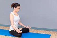 Mujer sana que ejercita yoga en el gimnasio del deporte Fotografía de archivo