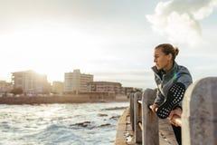 Mujer sana que estira en la verja en el camino de la playa Imagenes de archivo