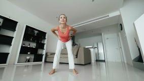 Mujer sana que hace ejercicio de la aptitud en entrenamiento de la mañana en el interior casero almacen de metraje de vídeo