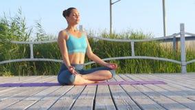 Mujer sana que medita en loto de la actitud encima en la manta púrpura almacen de metraje de vídeo
