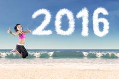 Mujer sana que salta con el número 2016 en la playa Imágenes de archivo libres de regalías