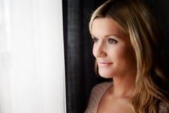 Mujer sana que se coloca en la ventana Fotos de archivo libres de regalías