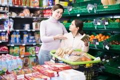 Mujer satisfecha con la hija que elige las galletas en supermercado Fotografía de archivo libre de regalías