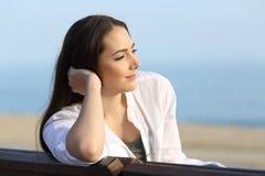 Mujer satisfecha pensativa que mira lejos en la playa Imagen de archivo libre de regalías