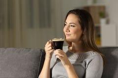 Mujer satisfecha que goza del café en la noche fotos de archivo libres de regalías
