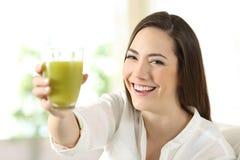 Mujer satisfecha que muestra un vidrio de jugo vegetal fotos de archivo libres de regalías