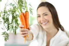 Mujer satisfecha que muestra zanahorias en casa imagen de archivo libre de regalías