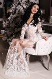 Mujer sensual con el pelo oscuro que presenta al lado del árbol de navidad adornado imagenes de archivo
