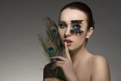 Mujer sensual con las plumas del pavo real Fotos de archivo